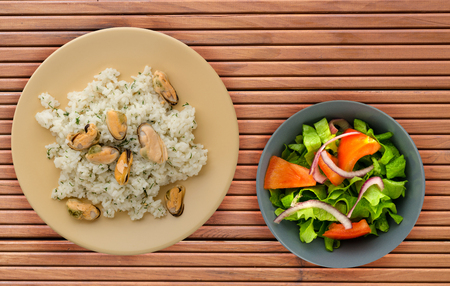 White rice with mussels on a plate. Rice with mussels on a wooden background. rice top view Imagens
