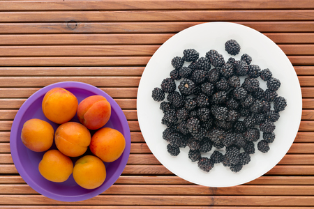 Blackberries on a plate on a wooden background. Vegetarian food. Healthy eating. Stockfoto