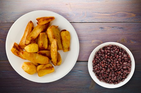 fry potatoes on a wooden background. fry potatoes on a plate Banco de Imagens