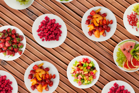 Fruit diet. Fruits on a plate on a wooden background. Healthy food . Imagens