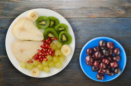 mélange de fruits (poire, kiwi, raisins, banane, grenade) sur un fond en bois. fruits sur une assiette