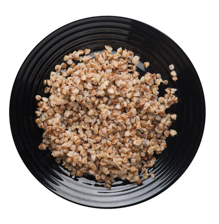 buckwheat in a black  plate isolated on white background. buckwheat top view. Healthy food. veretian food Stock Photo