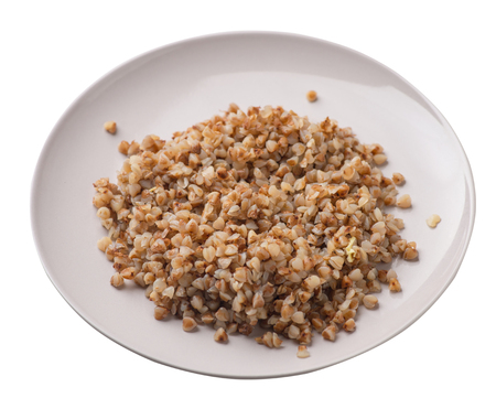 buckwheat in a beige plate isolated on white background. buckwheat top side view. Healthy food. veretian food