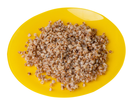buckwheat in a yellow   plate isolated on white background. buckwheat top side view. Healthy food. veretian food Stock Photo