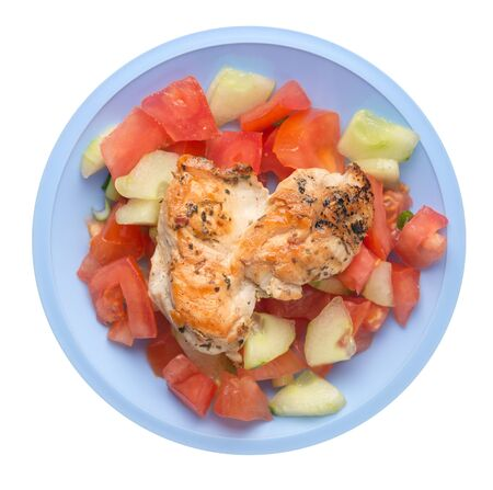 grilled chicken breast salad with tomato, cucumber and onion .grilled chicken breast on a light blue plate isolated on white background. grilled chicken breast top view Stock Photo