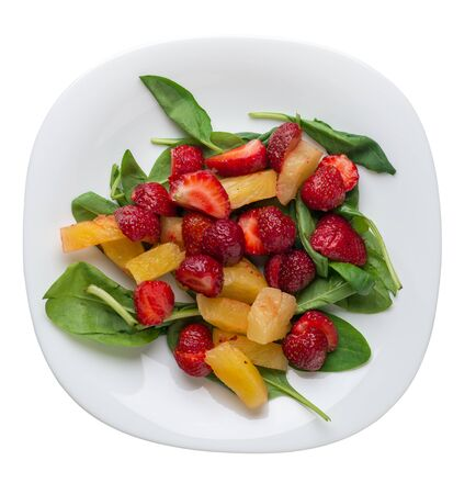 salad with strawberries, pineapple and spinach on a white  plate. fruit vegetarian salad isolated on white background. vegan salad top view