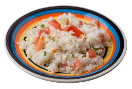 rice with vegetables on a multicolored plate isolated on white background . rice with tomatoes, cucumbers and onions .healthy breakfast  rice top side view