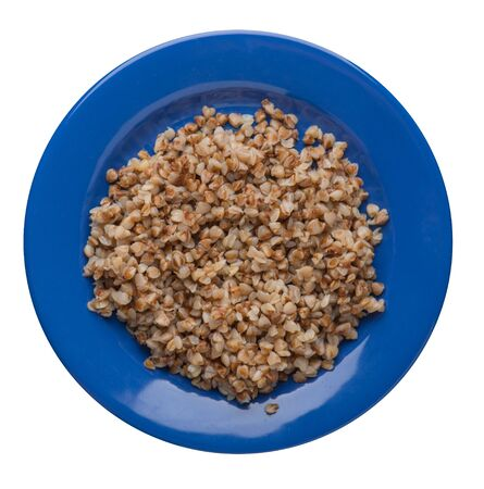 Buckwheat in a blue plate isolated on white background. Buckwheat top view. Healthy food.