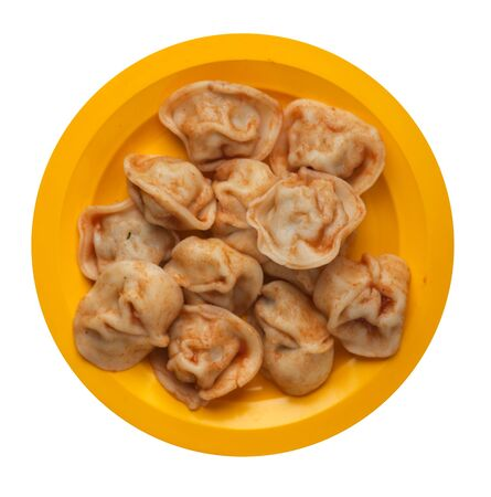 dumplings on a yellow  plate isolated on white background. dumplings in tomato sauce. dumplings top view