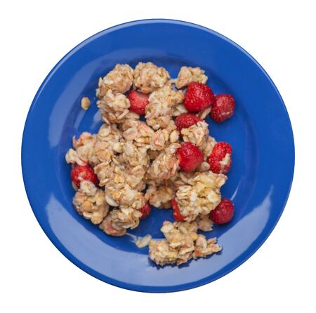 muesli with strawberries on a blue plate isolated on white background.healthy breakfast top view.diet food on a plate. Archivio Fotografico