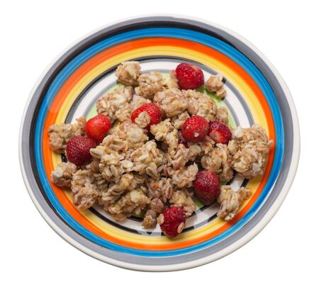 muesli with strawberries on a multicolored plate isolated on white background.healthy breakfast top side view.diet food on a plate.