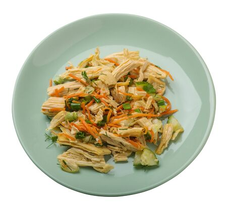 salad with soy asparagus and carrots, cucumbers and dumplings on a light green plate. vegetarian soy salad on a plate isolated on white background.