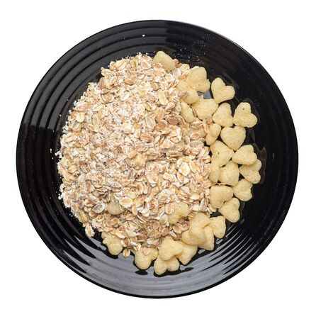 healthy breakfast on a black plate isolated on white background.muesli with cornflakes, raisins, dates, pears and pineapple dried cashew nuts. 免版税图像