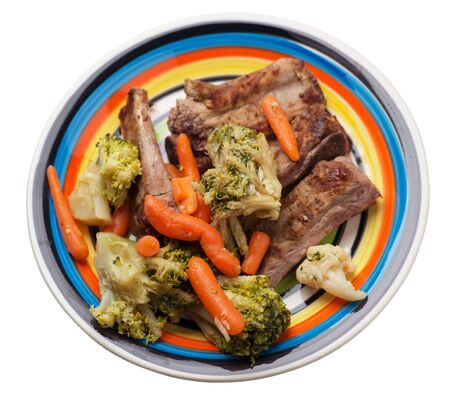 grilled pork ribs with broccoli cabbage, carrots and garlic on a multicolored plate. fried pork ribs with vegetables on a white background. hearty rustic food top side view 免版税图像