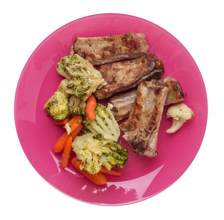 grilled pork ribs with broccoli cabbage, carrots and garlic on a pink  plate. fried pork ribs with vegetables on a white background. hearty rustic food top view