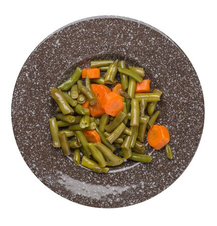 green beans with garlicand carrots  on a brown with a marble crumb  plate isolated on white background.green beans with carrot top view. healthy vegetarian food