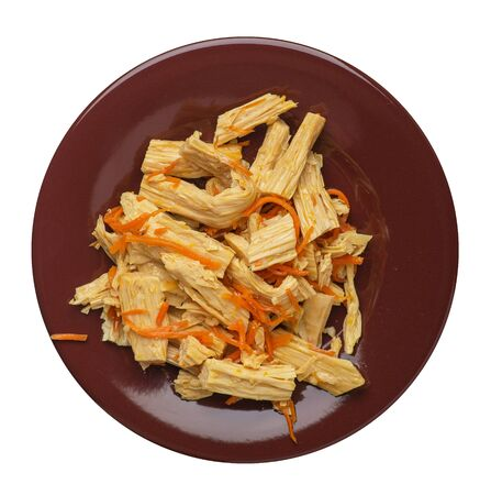 soy asparagus and carrot salad on a brown  plate. soy asparagus isolated on white background. Asian food top view. vegetarian food