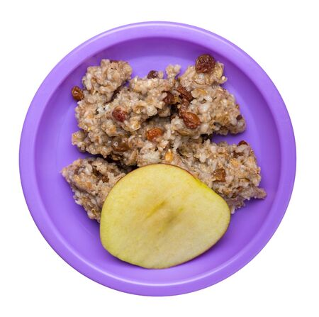 rye flakes with raisins and apples on a purple  plate. rage flakes isolated on white background. healthy breakfast top view Stock Photo