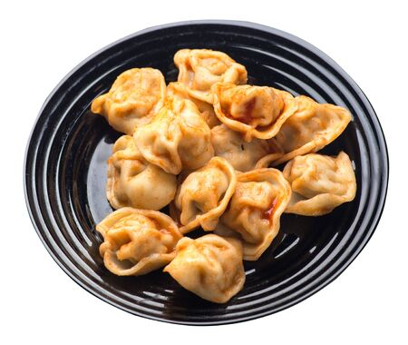 dumplings on a black  plate isolated on white background. dumplings in tomato sauce. dumplings top side  view