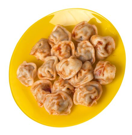 dumplings on a yellow plate isolated on white background. dumplings in tomato sauce. dumplings top side view
