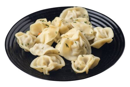 dumplings on a black  plate isolated on white background .boiled dumplings.meat dumplings top side view .pelmeni with dill