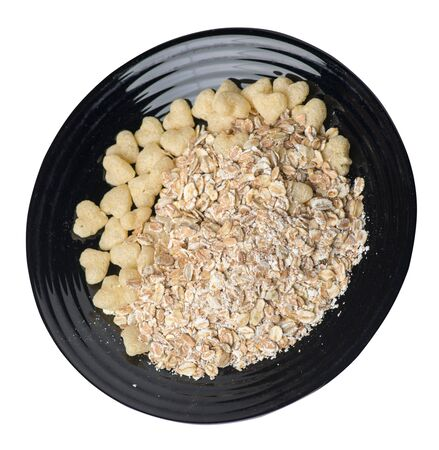 healthy breakfast on a black plate isolated on white background.muesli with cornflakes, raisins, dates, pears and pineapple dried cashew nuts.breakfast vegetarian top side view