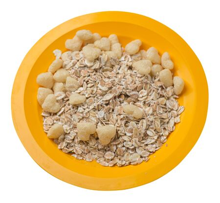 healthy breakfast on a yellow  plate isolated on white background.muesli with cornflakes, raisins, dates, pears and pineapple dried cashew nuts.breakfast vegetarian top side view