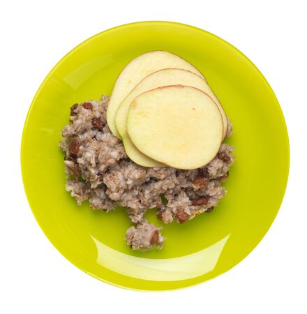 rye flakes with raisins and apples on a lime  plate. rage flakes isolated on white background. healthy breakfast top view