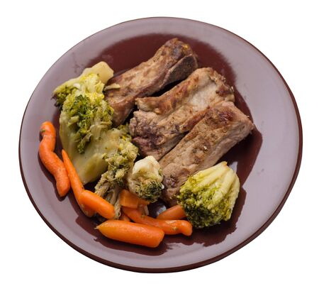 grilled pork ribs with broccoli cabbage, carrots and garlic on a brown  plate. fried pork ribs with vegetables on a white background. hearty rustic food top side view