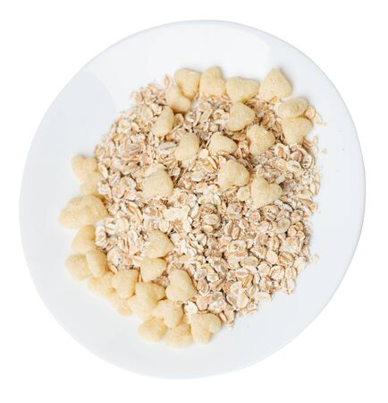 healthy breakfast on a white plate isolated on white background.muesli with cornflakes, raisins, dates, pears and pineapple dried cashew nuts.breakfast vegetarian top side  view
