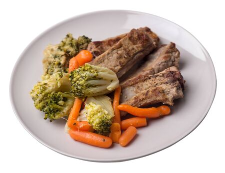 grilled pork ribs with broccoli cabbage, carrots and garlic on a light gray  plate. fried pork ribs with vegetables on a white background. hearty rustic food top side view 写真素材