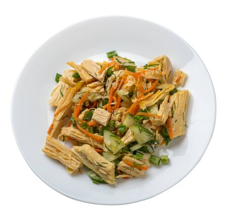 salad with soy asparagus and carrots, cucumbers and dumplings on a white  plate. vegetarian soy salad on a plate isolated on white background. healthy eating top side  view.