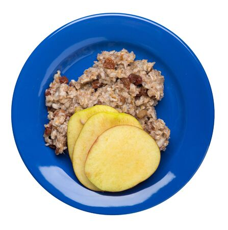 rye flakes with raisins and apples on a blue plate. rage flakes isolated on white background. healthy breakfast top view 写真素材