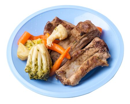 grilled pork ribs with broccoli cabbage, carrots and garlic on a light blue plate. fried pork ribs with vegetables on a white background. hearty rustic food top side view