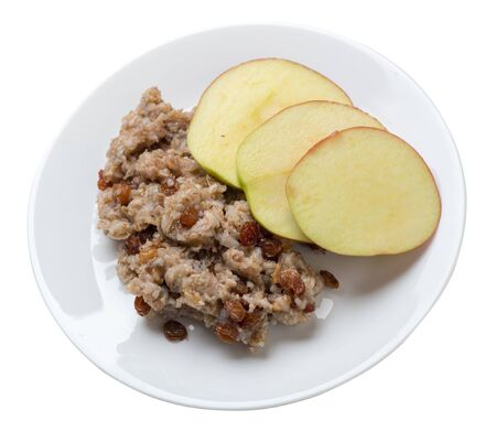 rye flakes with raisins and apples on a white plate. rage flakes isolated on white background. healthy breakfast top side  view 写真素材