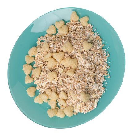 healthy breakfast on a turquoise plate isolated on white background.muesli with cornflakes, raisins, dates, pears and pineapple dried cashew nuts.breakfast vegetarian top side  view