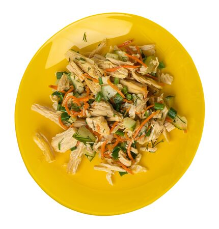 salad with soy asparagus and carrots, cucumbers and dumplings on a yellow plate. vegetarian soy salad on a plate isolated on white background. healthy eating top side  view.