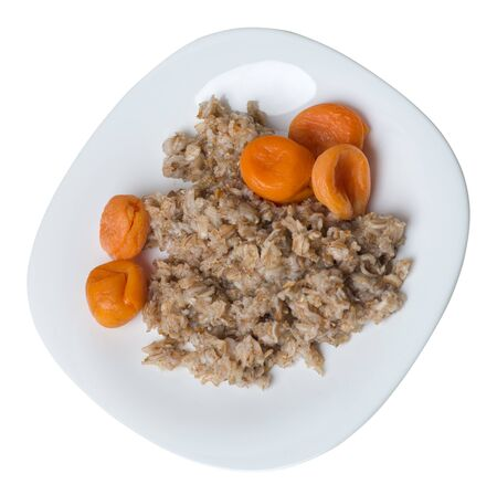Healthy food .rzhanye flakes with dried apricots on a white  plate. rainy flakes isolated on white background. top side view diet breakfast 写真素材