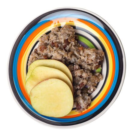 rye flakes with raisins and apples on a multicolored plate. rage flakes isolated on white background. healthy breakfast top side  view