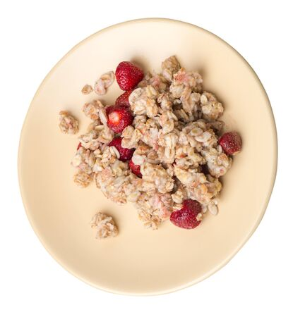 muesli with strawberries on a llight brown plate isolated on white background.healthy breakfast top side view.diet food on a plate.