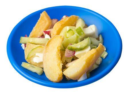 rodajas de patata con verduras en un plato azul aislado sobre fondo blanco. comida chatarra . comida rústica. patatas con verduras vista lateral superior.