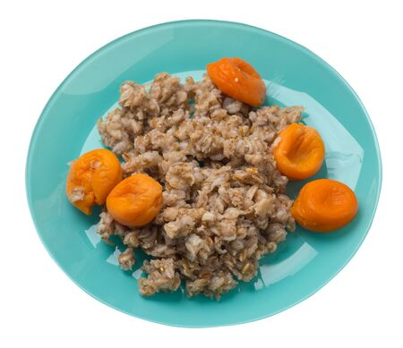 Healthy food .rzhanye flakes with dried apricots on a turquoise plate. rainy flakes isolated on white background. top view side diet breakfast
