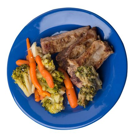 grilled pork ribs with broccoli cabbage, carrots and garlic on a blue plate. fried pork ribs with vegetables on a white background. hearty rustic food top side view