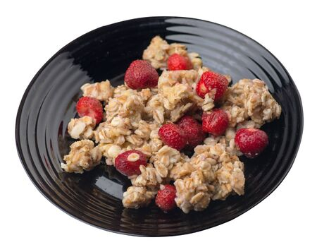 muesli with strawberries on ablack plate isolated on white background.healthy breakfast top side view.diet food on a plate. 写真素材