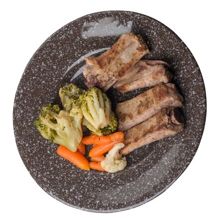 grilled pork ribs with broccoli cabbage, carrots and garlic on a brown with a marble crumb plate. fried pork ribs with vegetables on a white background. hearty rustic food top side view 写真素材