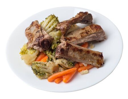 grilled pork ribs with broccoli cabbage, carrots and garlic on a white plate. fried pork ribs with vegetables on a white background. hearty rustic food top side view 写真素材