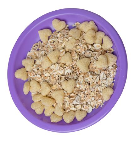 healthy breakfast on a purple plate isolated on white background.muesli with cornflakes, raisins, dates, pears and pineapple dried cashew nuts.breakfast vegetarian top side view 스톡 콘텐츠