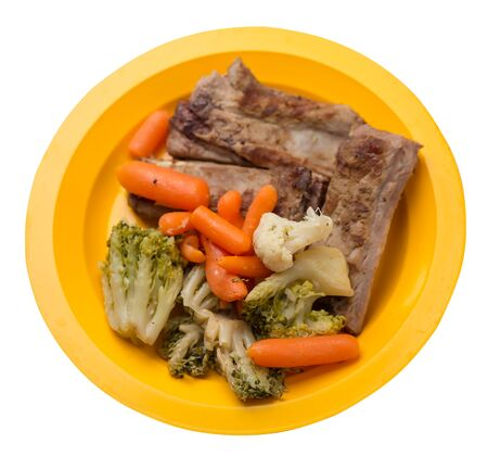 grilled pork ribs with broccoli cabbage, carrots and garlic on a yellow plate. fried pork ribs with vegetables on a white background. hearty rustic food top side view 写真素材
