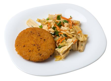 fishcake with soy asparagus and carrots, cucumbers and dilll. fish cutlet on a white plate isolated.fish cutlet with vegetables top side view