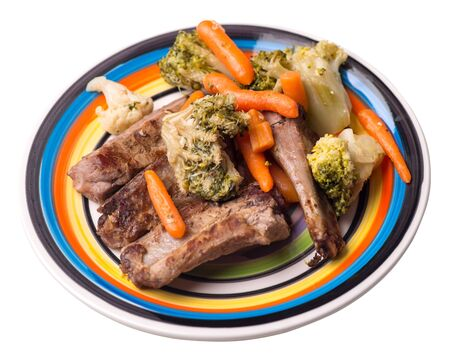 grilled pork ribs with broccoli cabbage, carrots and garlic on a multicolored plate. fried pork ribs with vegetables on a white background. hearty rustic food top side view Stock Photo - 129862253